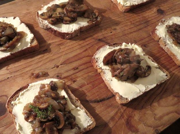 Geschmorte Champignon-Zwiebel-Pfanne mit wilden Kräutern auf geröstetem Brot mit Frischkäse
